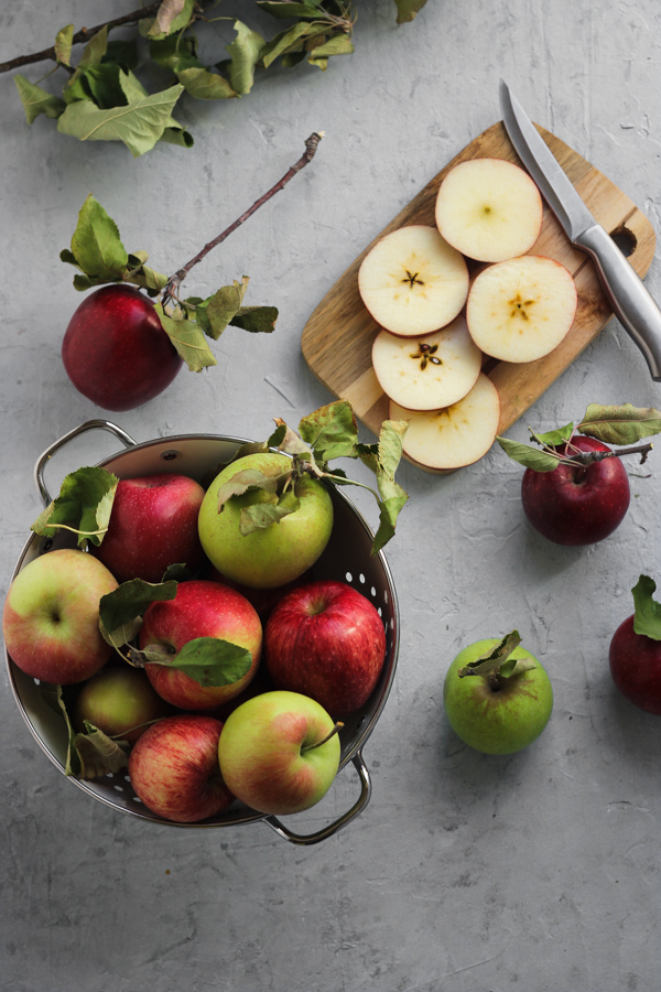 cut and whole apples in a bowl
