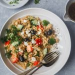 mediterranean quinoa salad in a bowl with dressing on the side