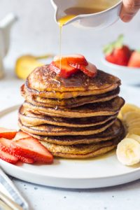 Healthy Banana Oat Pancake stacked on a plate topped with fruits